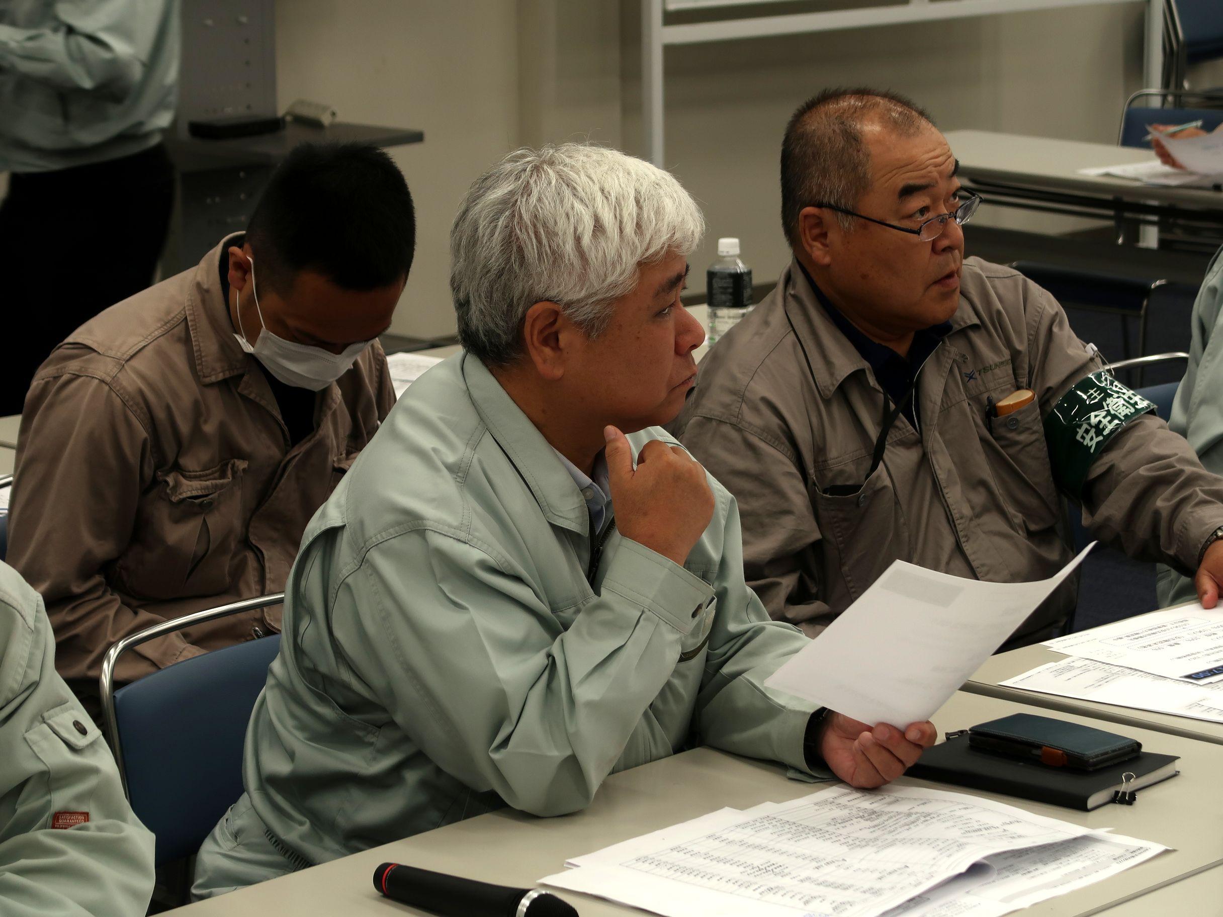 報告を受け、状況を把握、判断する岡本社長